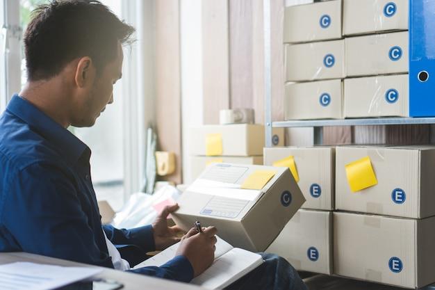 Concepto de negocio de comercio electrónico. vista posterior del propietario de un negocio que realiza el pedido del cliente.