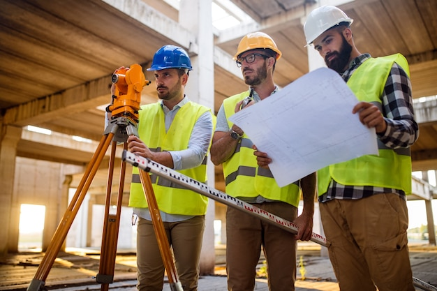 Concepto de negocio, construcción, trabajo en equipo y personas. grupo de ingenieros y arquitectos en cascos con planos en el sitio de construcción
