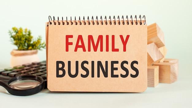 Concepto de negocio. cuaderno con hoja de papel blanco de la empresa familiar de texto para notas, calculadora, bloques de madera, lupa, en el fondo