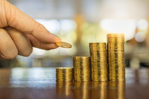 Concepto de negocio, dinero, finanzas y ahorro. ciérrese para arriba de la tenencia de la mano del hombre y ponga una moneda para apilar de monedas en la tabla de madera.