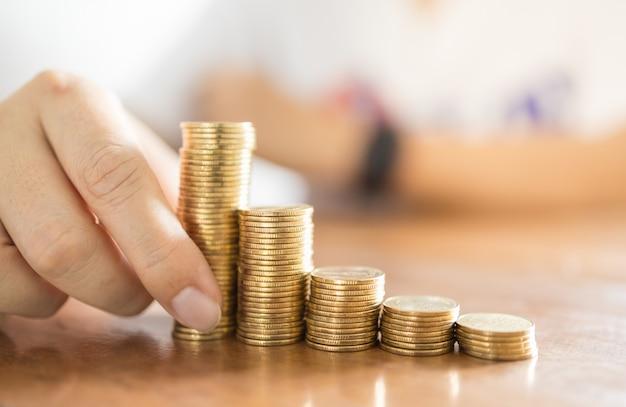 Concepto de negocio, dinero, finanzas, riesgo, seguro y ahorro. ciérrese para arriba de la mano del hombre que sostiene la pila inestable de monedas de oro en la tabla de madera.