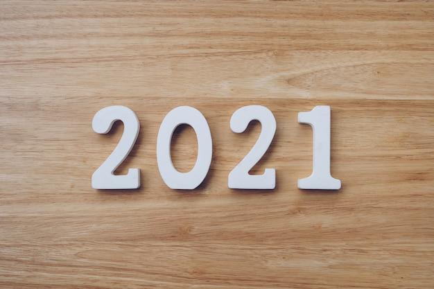 Concepto de negocio y diseño - número de madera 2021 para texto de feliz año nuevo en la mesa de madera.