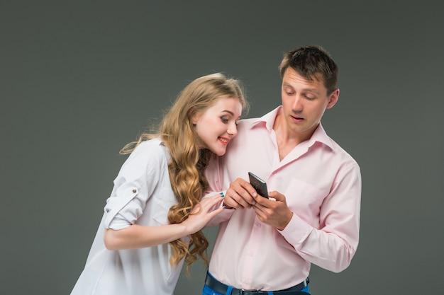 Concepto de negocio. los dos jóvenes colegas sosteniendo teléfonos móviles en la pared gris
