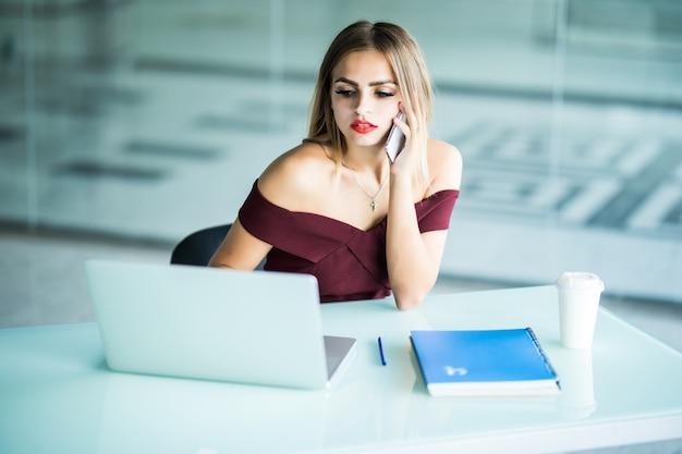 Concepto de negocio - empresaria hablando por teléfono en la oficina