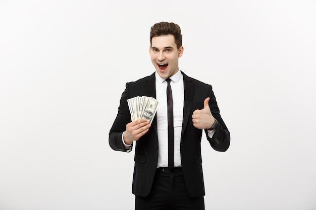 Concepto de negocio - empresario exitoso sosteniendo billetes de un dólar y mostrando el pulgar hacia arriba aislado sobre fondo blanco.