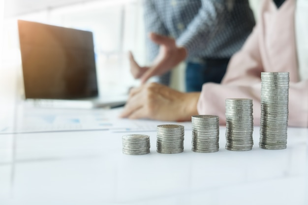 Concepto de negocio. filas de monedas para el concepto de finanzas y banca con hombre de negocios y mujer. una metáfora de la consultoría financiera internacional.