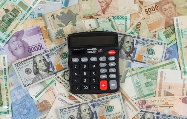 Concepto de negocio y financiero con calculadora en pila de fondo plano de dinero endecha.