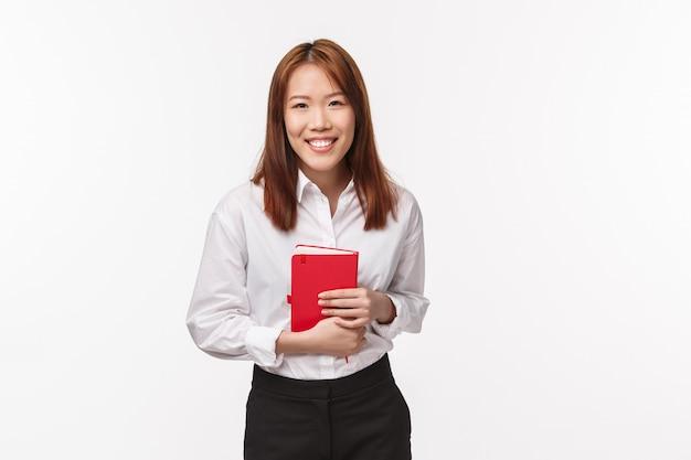 Concepto de negocio, finanzas y carrera. exitosa elegante joven asiática trabajadora de oficina en camisa y falda, mantenga portátil riendo y sonriendo complacido, de pie