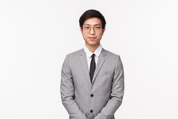 Concepto de negocio, finanzas y carrera. retrato de hombre asiático joven guapo profesional en traje gris y corbata, se ve determinado, educadamente sonriente, reunirse con socios de la empresa en la pared blanca