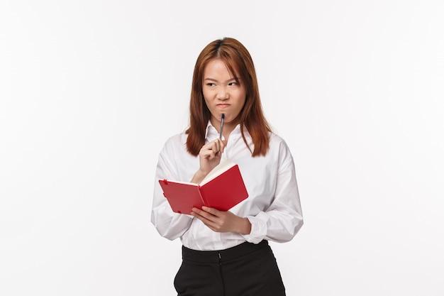 Concepto de negocio, finanzas y carrera. retrato de mujer asiática reacia y molesta en camisa, haciendo muecas molesto, pensando, no le gusta preparar el proyecto, morder la pluma y sostener el cuaderno