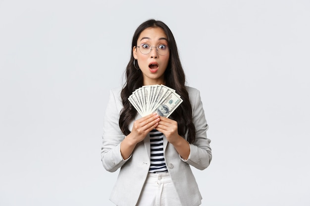 Concepto de negocio, finanzas y empleo, empresario y dinero. la joven empresaria asiática sorprendida y sin palabras gana el primer cheque de pago por vender una casa, guardar dinero en efectivo y mirar asombrada.