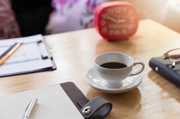 Concepto del negocio y de las finanzas del funcionamiento de la oficina, cierre encima de la taza de café en el escritorio en día laborable.