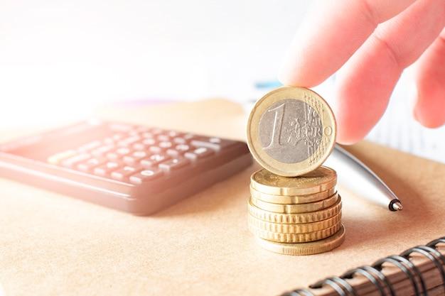 Concepto de negocio, finanzas o inversión. monedas, chequera o cuaderno y pluma estilográfica, calculadora.