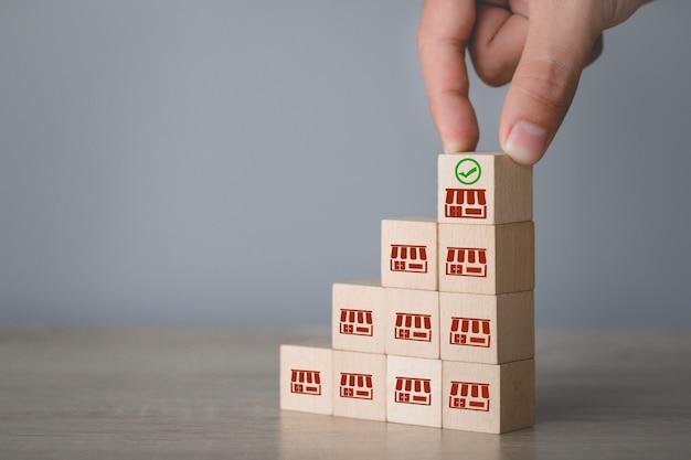 Concepto de negocio de franquicia, mano elegir blog de madera con marketing de franquicia.