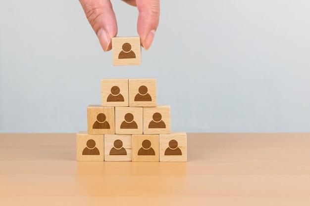 Concepto de negocio de gestión de recursos humanos y reclutamiento, mano poniendo bloque de cubo de madera en la pirámide superior, espacio de copia