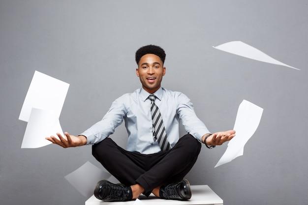 Concepto del negocio - hombre de negocios afroamericano profesional joven hermoso que tira lejos la pila de papelería que vuela en el aire.