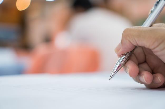 Concepto de negocio: hombre de negocios de la mano que sostiene la pluma de plata para tomar notas en el papeleo blanco o documento en la sala de reuniones de la conferencia en el seminario sobre personas borrosas en el interior