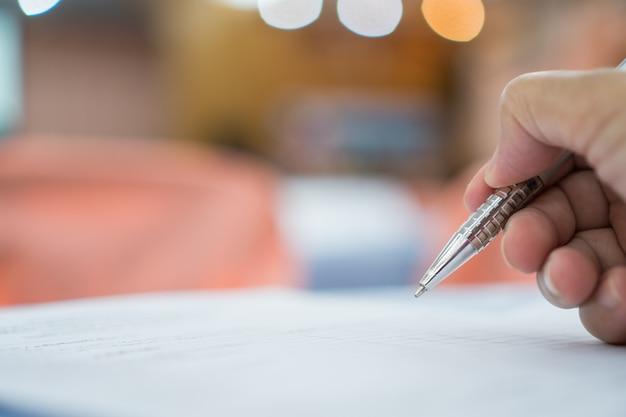 Concepto de negocio: hombre de negocios de la mano que sostiene la pluma de plata para tomar notas en el papeleo blanco