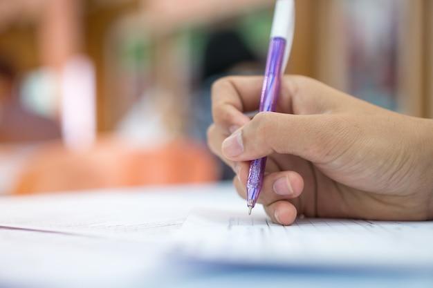 Concepto del negocio, hombre de negocios de la mano que sostiene la pluma de plata a tomar notas en el papeleo blanco