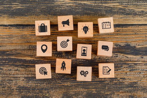 Concepto de negocio con iconos en cubos de madera en mesa de madera plana lay.
