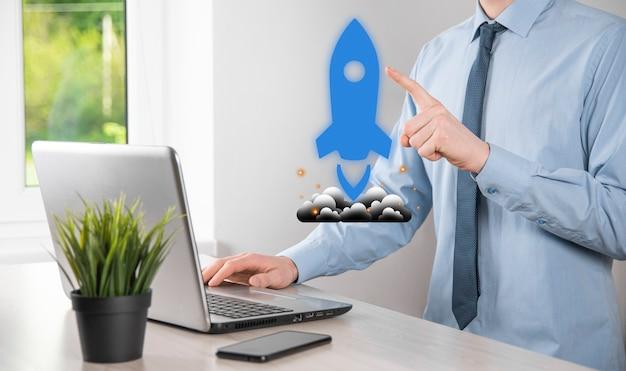 El concepto de negocio de inicio, el empresario sosteniendo la tableta y el cohete de icono se está lanzando y se dispara volando desde la pantalla con conexión de red sobre fondo oscuro.