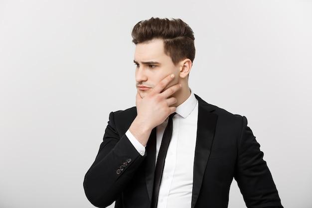Concepto de negocio joven empresario guapo en traje pensando con la mano en la barbilla estrategias de negocio c ...