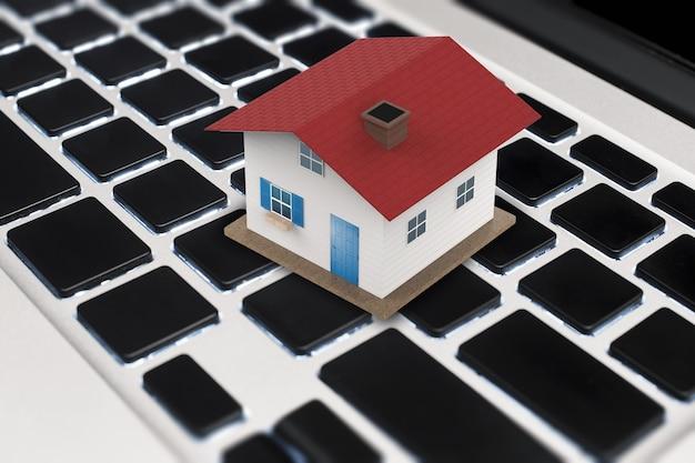 Concepto de negocio en línea con simulacro de casa de techo rojo en el teclado