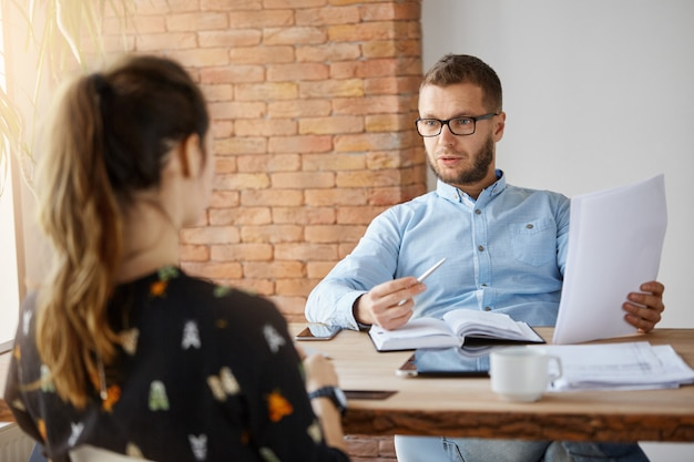 Concepto de negocio. maduro barbudo serio director de empresa masculino sentado en la oficina frente a la chica de cabello oscuro que vino a la entrevista de trabajo mirando a través de los documentos, hablando sobre la experiencia laboral.