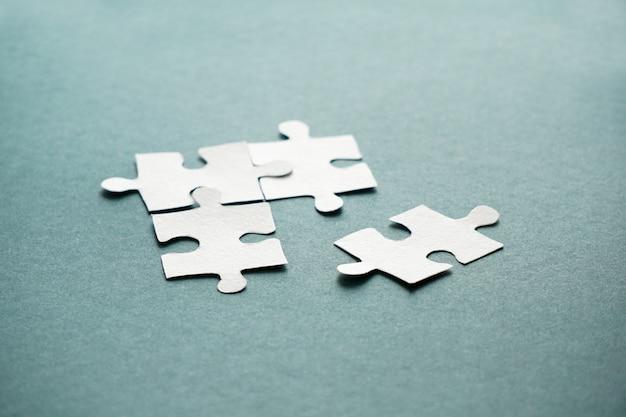 Concepto de negocio, manos de mujeres sosteniendo piezas de un rompecabezas blanco en el fondo azul