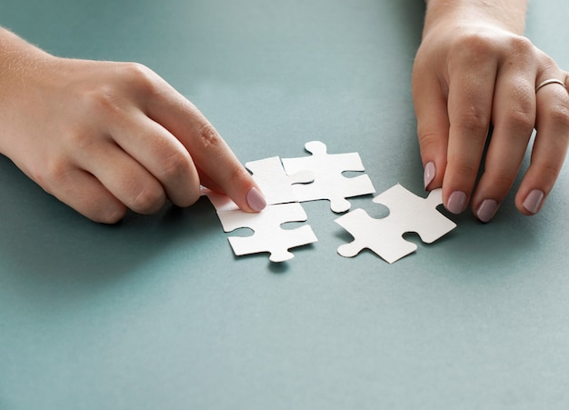 Concepto de negocio, manos de mujeres sosteniendo piezas de un rompecabezas blanco