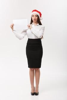 Concepto de negocio - mujer de negocios confiada joven hermosa con el sombrero de santa que sostiene el papel en blanco blanco con la expresión facial sorprendente.