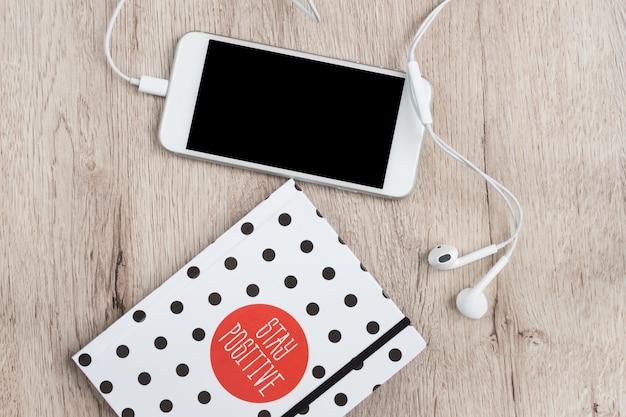 Concepto de negocio y oficina - cuaderno de tapa de lunares, smartphone y auriculares en mesa de madera. mínima endecha plana, vista superior.