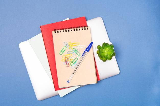 Concepto de negocio de oficina o educación: vista superior portátil, cuaderno, papelería y planta de casa pequeña sobre fondo azul. copia espacio espacio libre.
