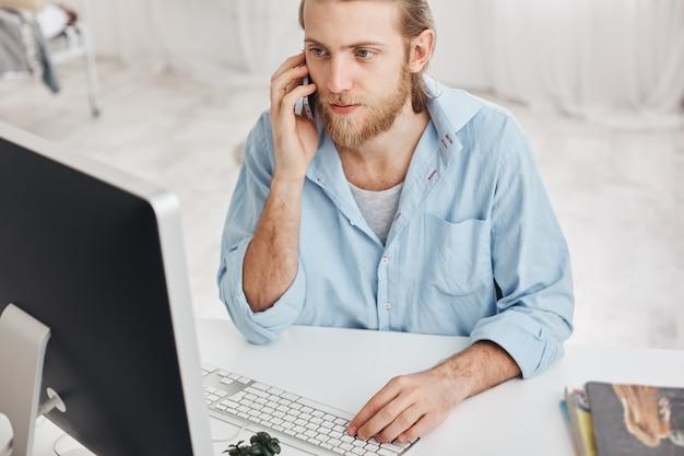 Concepto de negocio, oficina y tecnología. vista superior del empleado barbudo con camisa azul, hablando por teléfono con compañeros, escribiendo en el teclado, mirando en la pantalla de la computadora, utilizando dispositivos modernos