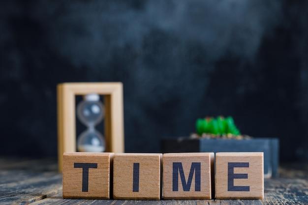 Concepto de negocio con palabra de tiempo en cubos de madera, reloj de arena y planta