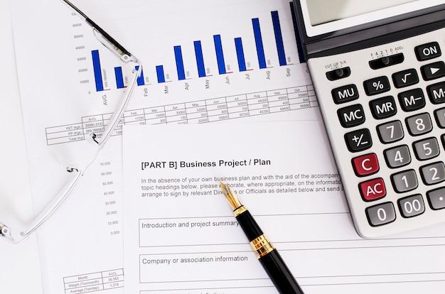 Concepto de negocio con pluma y anteojos y calculadora en plan de negocios
