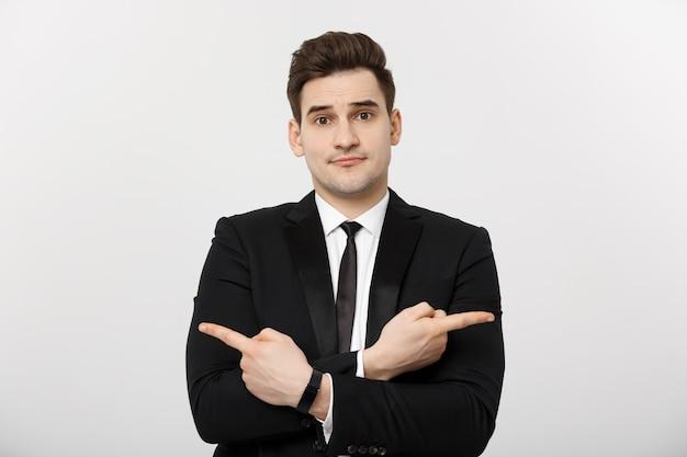 Concepto de negocio retrato apuesto joven empresario señalar con el dedo en el lado para vacío concepto de espacio de copia ...