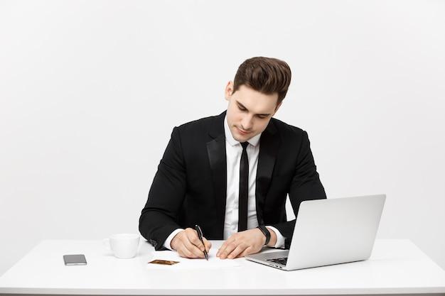 Concepto de negocio retrato concentrado joven empresario exitoso escribiendo documentos en oficina brillante ...