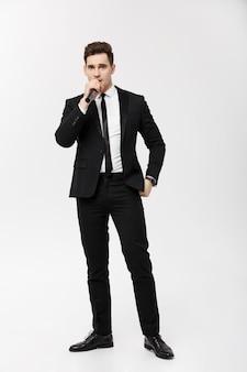Concepto de negocio: retrato de cuerpo entero joven en traje negro sostiene un micrófono, canta y posa sobre un fondo blanco.
