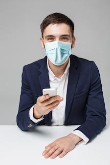 Concepto de negocio - retrato guapo hombre de negocios guapo feliz en mascarilla jugando teléfono móvil y sonriendo con la computadora portátil en la oficina de trabajo