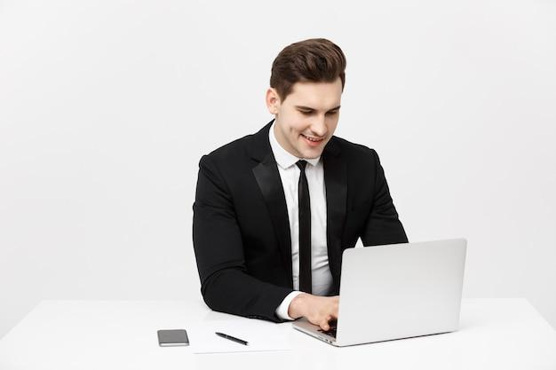 Concepto de negocio: retrato de hombre de negocios atractivo feliz trabajando en la computadora portátil en la oficina