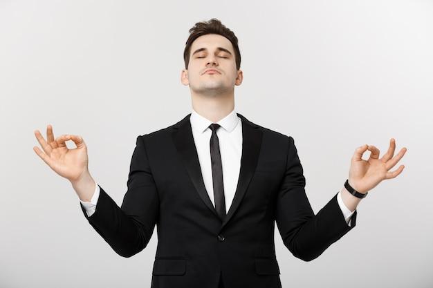 Concepto de negocio - retrato de hombre de negocios caucásico guapo haciendo meditación y yoga antes de trabajar