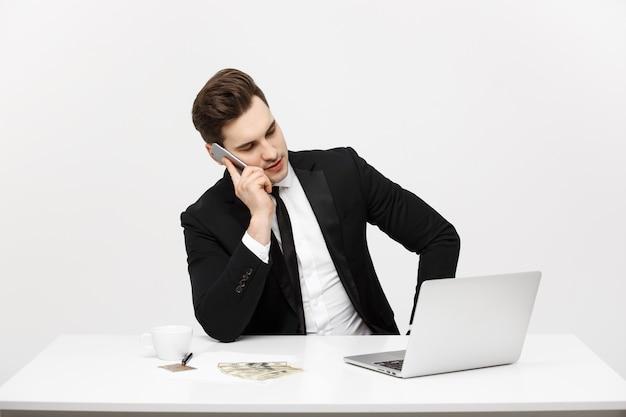 Concepto de negocio retrato joven empresario exitoso que trabaja en la oficina brillante usando la computadora portátil hablando ...