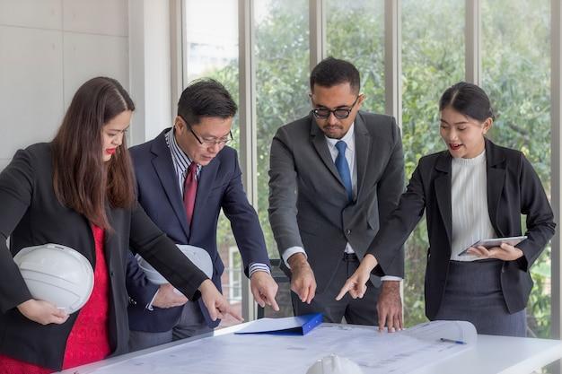 Concepto de negocio; reunión del equipo de ingenieros para discutir el plano en su oficina.