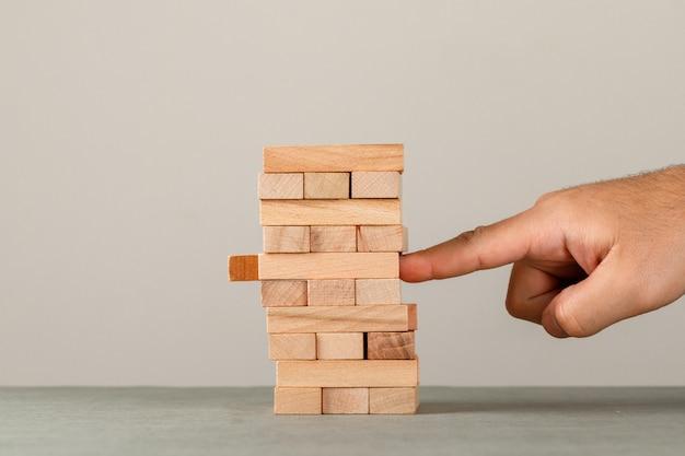 Concepto de negocio y riesgo y gestión en vista lateral de pared gris y blanco. dedo empujando la torre de bloques de madera.