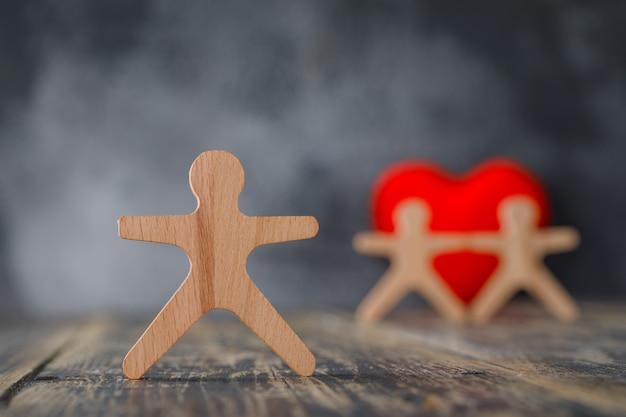 Concepto de negocio y seguridad con figuras de madera de personas, vista lateral de corazón rojo.