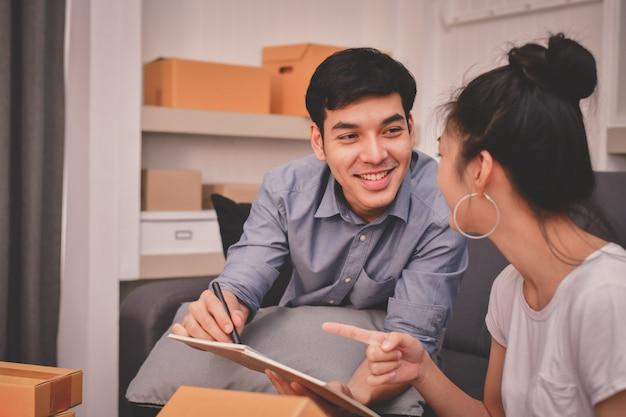 Concepto de negocio de sme jóvenes asiáticos están empacando sus paquetes.