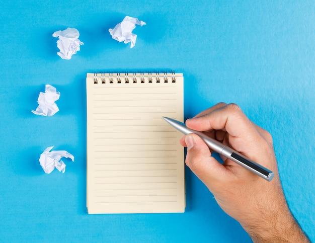Concepto de negocio con tacos de papel arrugado sobre fondo azul completamente endecha. empresario tomando notas en papel.