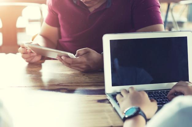 Concepto de negocio y tecnología. primer de la gente que usa el ordenador portátil y el móvil en café.