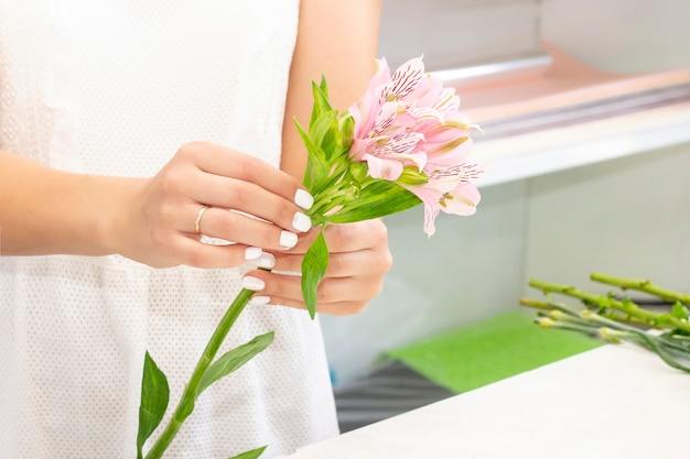 Concepto de negocio, venta y floristería - cerca de mujer floristería sosteniendo ramo en la tienda de flores. tonos suaves de flores frescas de primavera.